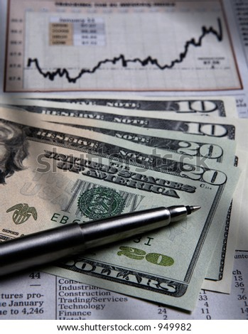 Shot of US currencies and a newspaper showing a financial chart