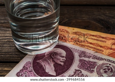 Shot of vodka with money of the Soviet Union on an old wooden table. Close up view