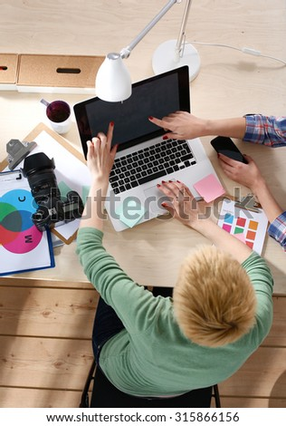 Shot of women pointing at the laptop in a home office