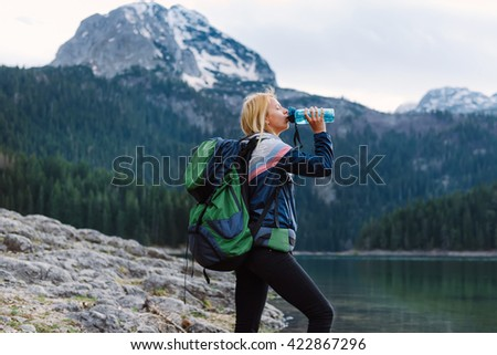 Shot of young female traveler taking a break from her hike and drinking water - stock photo