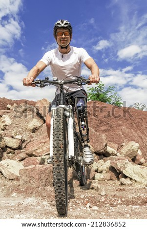 Shot of young male mountain bike rider with leg prosthesis between rocks.  - stock photo