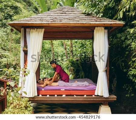 Shot of young man and woman receiving massage at health spa in luxury resort. Couple at outdoor spa center and having body massage. Outdoor spa center at luxury resort. - stock photo