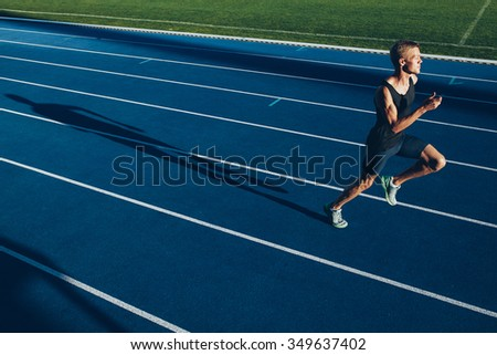 Shot of young professional sprinter running on racetrack. Runner practicing his run on athletics running track. - stock photo