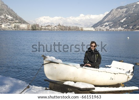 Shot of young woman sitting in snow covered boat at the lake of Zell am See in Austria. - stock photo