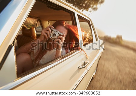 Shot of  young woman taking photos while sitting in a car. Female capturing a perfect road trip moment. - stock photo
