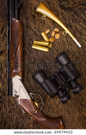 shotgun, cartridges, binoculars and hunt on top of a boar skin - stock photo