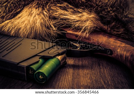 Shotgun lying next to the animal's fur produced and magazine with green cartridges 12 gauge. View close-up, focus on the magazine, image vignetting and the yellow-blue toning - stock photo