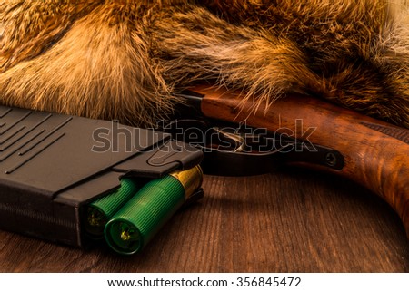 Shotgun lying next to the animal's fur produced and magazine with green cartridges 12 gauge. View close-up, focus on the magazine - stock photo