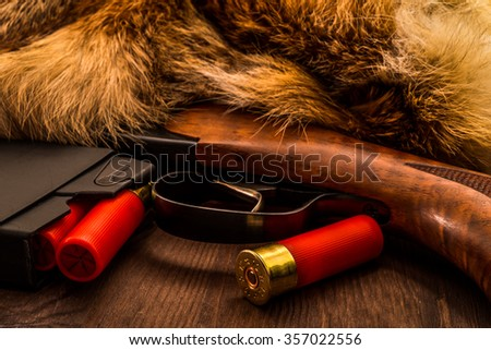 Shotgun lying next to the animal's fur produced and magazine with red cartridges 12 gauge. View close-up, focus on the magazine - stock photo