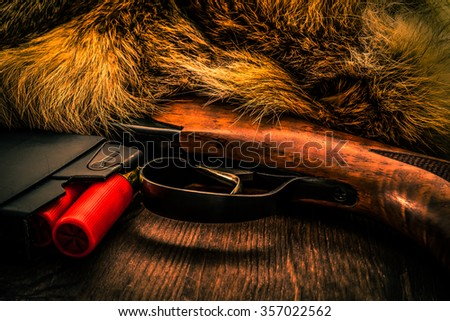 Shotgun lying next to the animal's fur produced and magazine with red cartridges 12 gauge. View close-up, focus on the magazine, image vignetting and the orange-blue toning - stock photo
