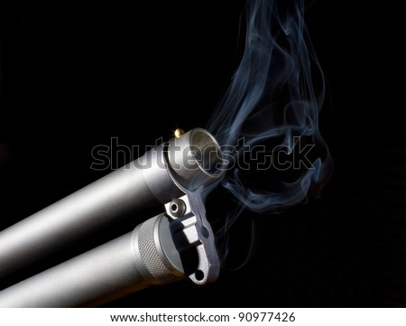 Shotgun that is pouring out smoke from the front of its barrel - stock photo