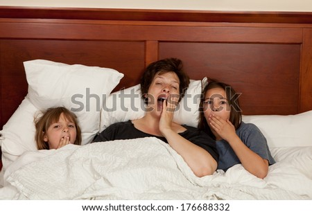 Shots of a mother and her two daughters yawning in bed with white linens part of a series - stock photo