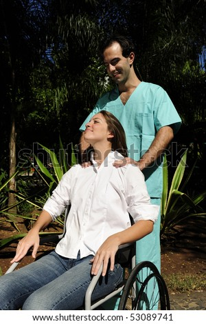 shoulder massage: healthcare worker and  woman in a wheelchair - stock photo