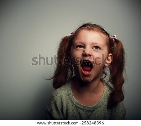 Shouting angry kid girl with open mouth and negative look on dark background - stock photo