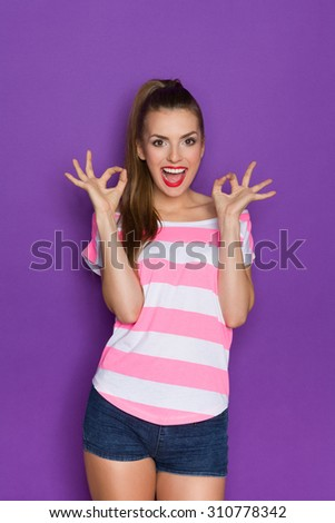 Shouting beautiful young woman in pink striped shirt and jeans shorts standing with arms raised and showing ok sign. Three quarter length studio shot on violet background. - stock photo