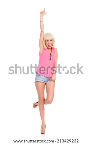 Shouting blonde young woman in high heels and pink top standing on one leg and pointing up. Full length studio shot isolated on white. - stock photo