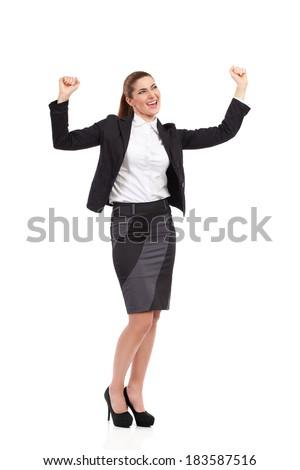 Shouting businesswoman in black suit raising hands. Full length studio shot isolated on white. - stock photo