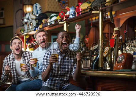 Shouting fans with beer in bar