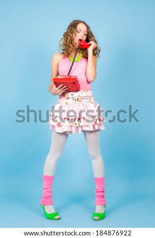 Shouting pin-up woman with red telephone standing on the blue background - stock photo