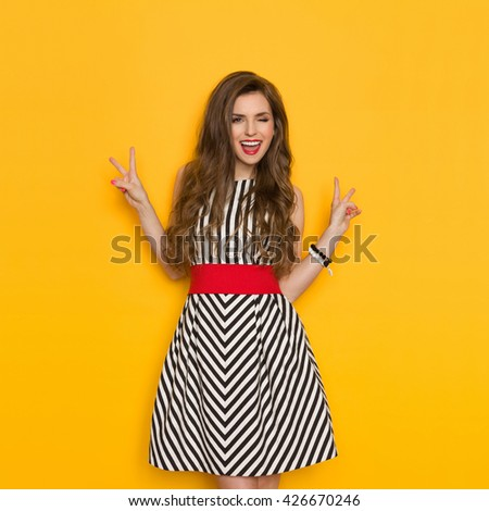 Shouting young woman in elegant striped dress winking and showing two finger or peace sign. Three quarter length studio shot on yellow background. - stock photo