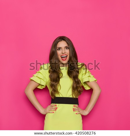 Shouting young woman in lime green dress posing with hands on hip and looking at camera. Waist up studio shot on pink background. - stock photo