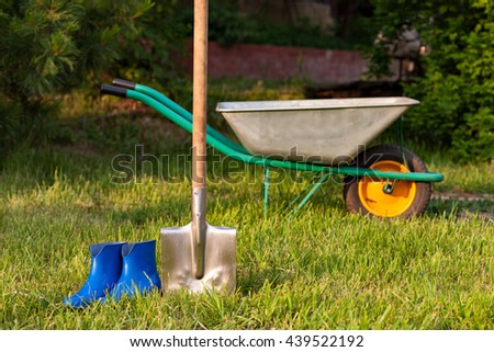 shovel and rubber boots. Garden tools on a green lawn..