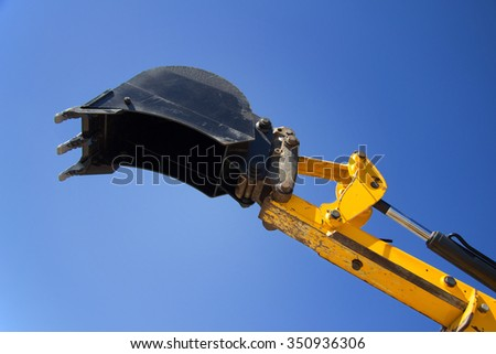 Shovel bucket against the blue sky, lift loads, construction machinery, construction machinery manipulator, unloading cargo, hydraulic capture truck, farm equipment, heavy tractor yellow. - stock photo