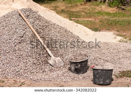 shovel is lying on a pile of gravel and two typed buckets - stock photo