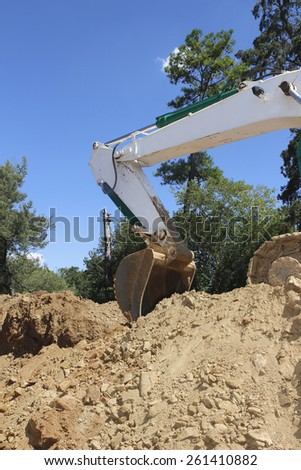 Shovel of a excavator against a blue sky - stock photo