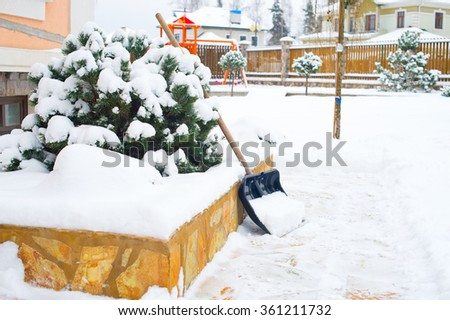 Shovel on snow in winter back yard of country house ready to clean the roads - stock photo