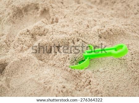 shovel toy on white sand - stock photo