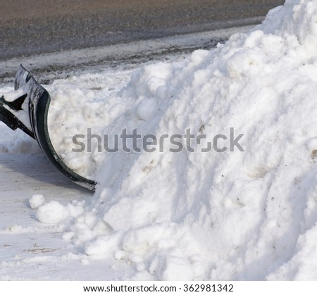 Shoveling Snow Driveway Fresh Snow Removal Background - Closeup snow shovel shoveling snow in a driveway, white winter snow pile background photo. - stock photo