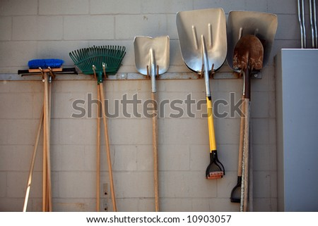 shovels, rakes, brooms hang on a wall - stock photo
