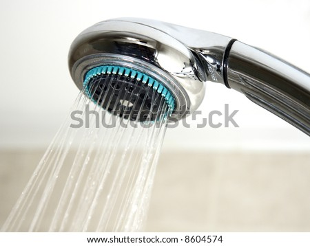 Shower head and running water in the bathroom - stock photo