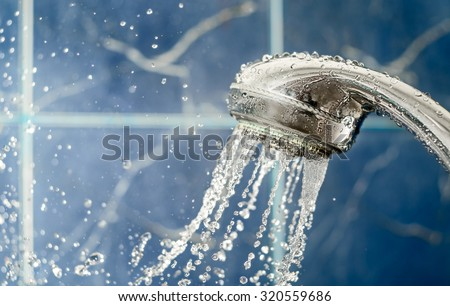 Shower head with water splashing out on blue background, copy space. Fresh liquid concept water drops levitating photo, copy-space - stock photo