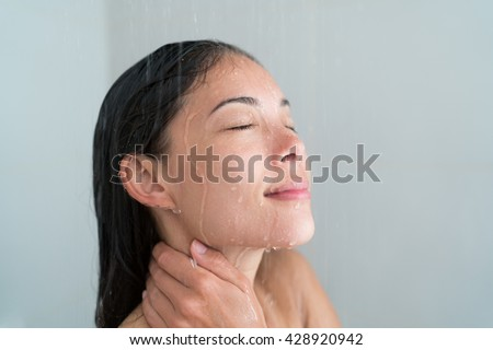 Shower woman showering relaxing under water massaging neck in hot shower. Asian female adult face enjoying spa relaxation time relaxing meditating in warm bath cleaning face and body at home. - stock photo