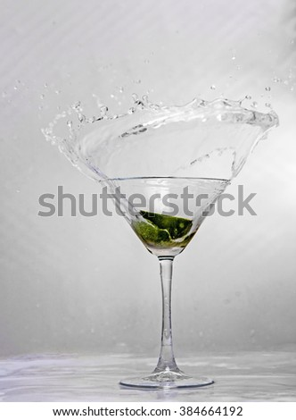 Showing a glass with a lime segment being dropped into it - stock photo