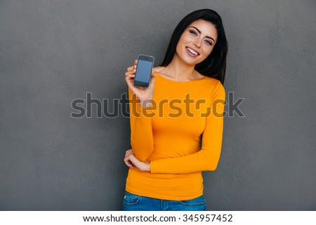 Showing her new smart phone. Attractive young woman showing her smart phone and smiling while standing against grey background - stock photo