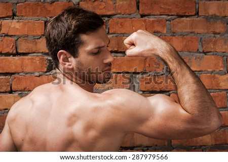 Showing his perfect bicep. Rear view of confident young muscular man posing while standing against brick wall  - stock photo
