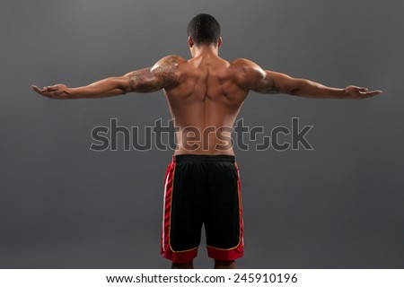 Showing his perfect muscles. Rear view of young shirtless African man stretching hands and looking away to copy space while standing against grey background  - stock photo