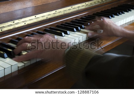 Showing movement with a slow shutter speed - old hands playing the piano