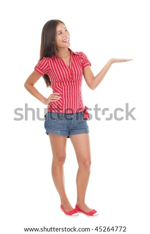 Showing product in full length. Young beautiful casual college student holding her arm out and presenting your product with open hand. Gorgeous mixed race chinese / caucasian model isolated on white. - stock photo