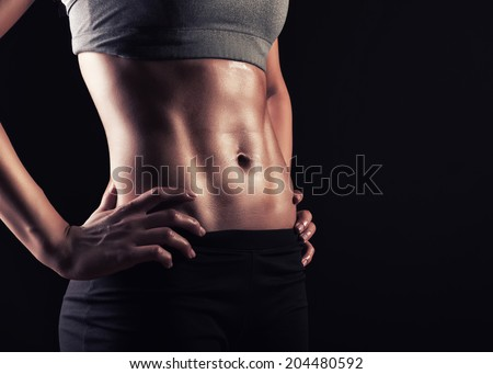 Showing some strong abs and flat belly - stock photo