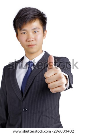 Showing thumb young Asian business man isolated on white background - stock photo