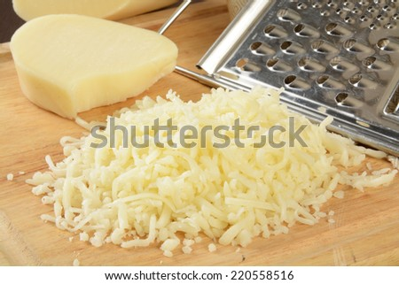 Shredded mozzarella cheese on a cutting board with a grater - stock photo