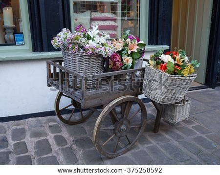SHREWSBURY, UNITED KINGDOM - JANUARY 30, 2016 - Gift Craft shop with a wheelbarrow floral display outside, Butchers Row, Shrewsbury, Shropshire, England, UK, Western Europe, January 30, 2016.
