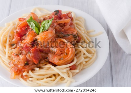shrimp cooked in wine tomato sauce with fresh basil over spaghetti pasta - stock photo