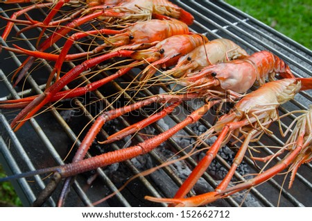 Shrimp grill on kiln with flames in background