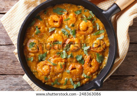 Shrimp in curry sauce in a pan close-up. horizontal view from above  - stock photo