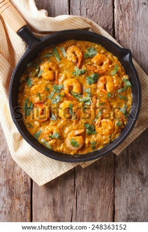 Shrimp in curry sauce in the pan. Vertical view from above